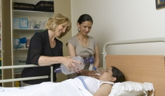 image for Two nurses helping a patient in hospital