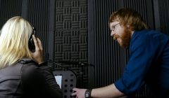 image for Woman speaking into a microphone while a man watches.